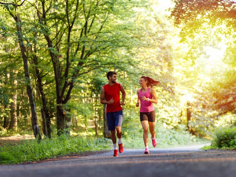 Man en vrouw lopen hard in het bos