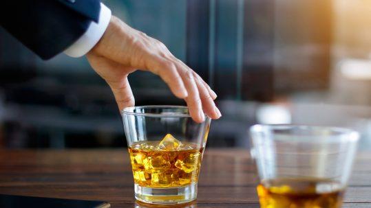 Man pakt een glas whiskey