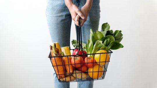 Vrouw houdt mand met groenten vast