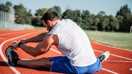 Sporter aan het stretchen op atletiekbaan